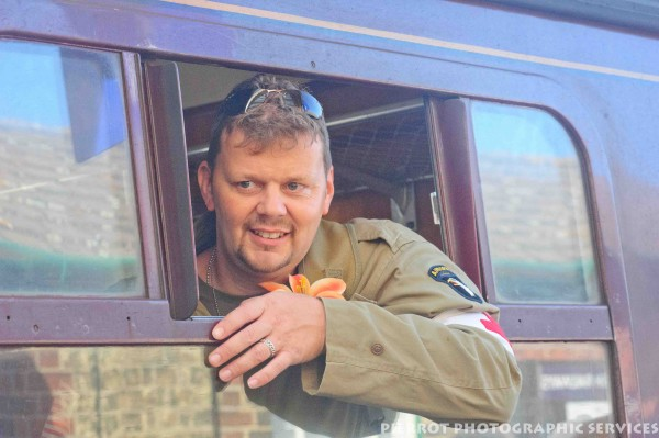 Man in US military uniform at train window at 1940s weekend in Sheringham
