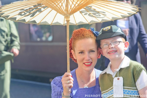 Attractive woman with umbrella with young evacuee boy at the 1940s weekend in Sheringham, North Norfolk 2012