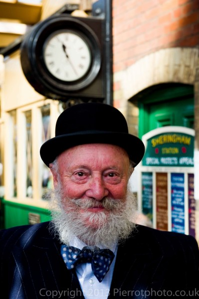 Old man with beard under station clock