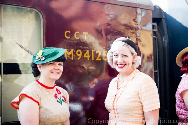 Two attractive women by railway carriage