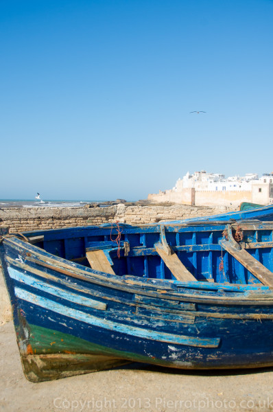 Upturned boat at the port of Essaouira, Morocco, looking towards the walled city