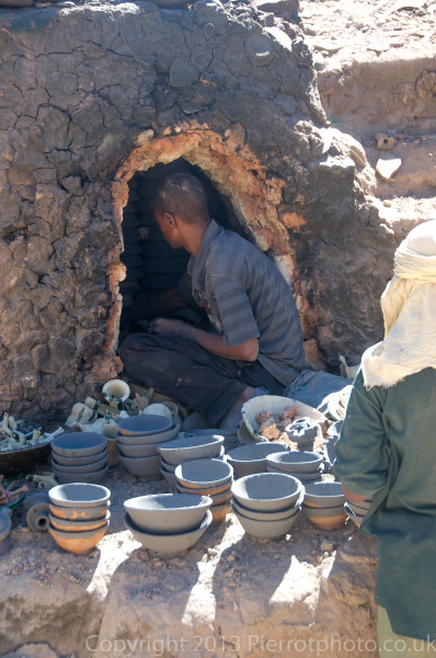 Moroccan potter putting pots into outdoor kiln