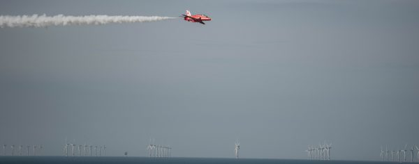 Red Arrow Hawk trainer flying with wind farm in the background at Cromer carnival